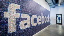 The Facebook logo is seen posted on a wall as a woman walks down a hallway. (©AFP/Jonathan Nackstrand)