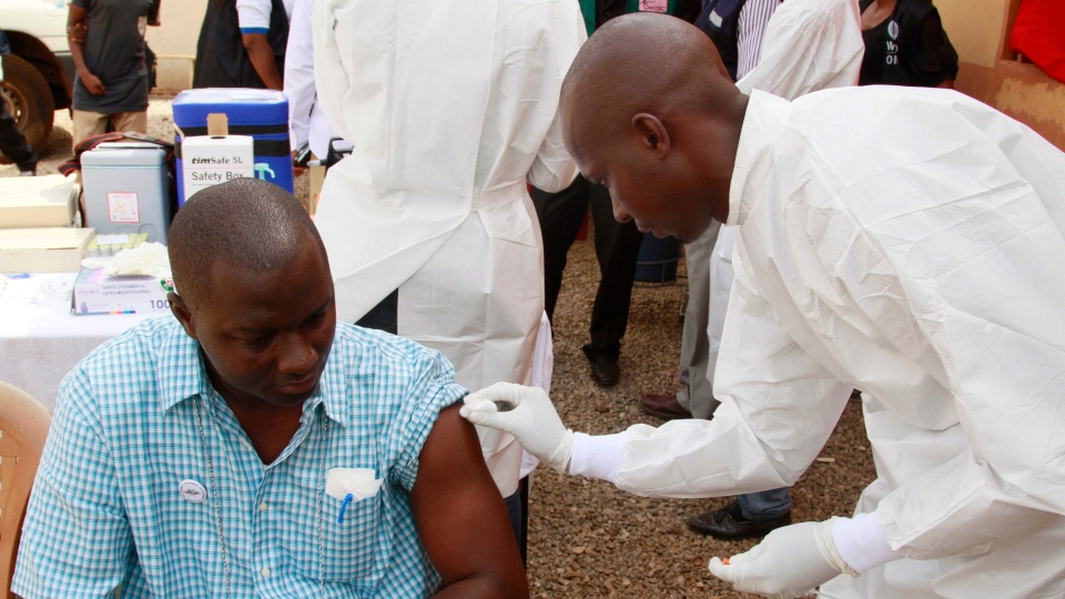 A health worker, right, cleans a man's arm before injecting him with a Ebola vaccine in Conakry, Guinea on March 7, 2015. (AP / Youssouf Bah)