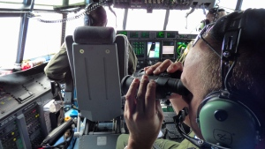 Petty Officer 1st Class Mike Crosby, right, scans the Atlantic while searching for missing Florida teens Perry Cohen and Austin Stephanos on Tuesday, July 28, 2015. The U.S. Coast Guard says it's suspending its search at sunset Friday. (Senior Chief Petty Officer Sarah B. Foster/U.S. Coast Guard via AP)