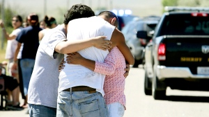 Family members embrace at the scene of a shooting in Pryor, Mont., on the Crow Reservation on Wednesday, July 29, 2015. (Casey Page / The Billings Gazette)