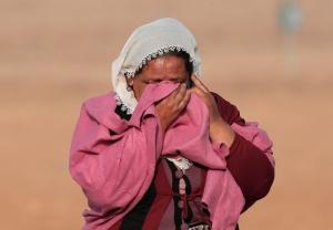 In this Monday, Oct. 13, 2014 file photo, Syrian Kurd Kiymet Ergun, 56, weeps standing in Mursitpinar, on the outskirts of Suruc, Turkey. (AP/Lefteris Pitarakis)