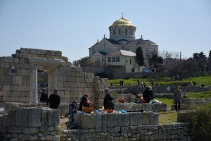 In this photo taken on Sunday, April 12, 2015, people gather at the area that was the ancient Greek colony of Chersonesus, and with the St. Vladimir's Cathedral in the background, just outside Sevastopol, the main port city in Crimea, the Black Sea Peninsula annexed by Russia from Ukraine last year. (Alexander Polegenko / AP Photo)
