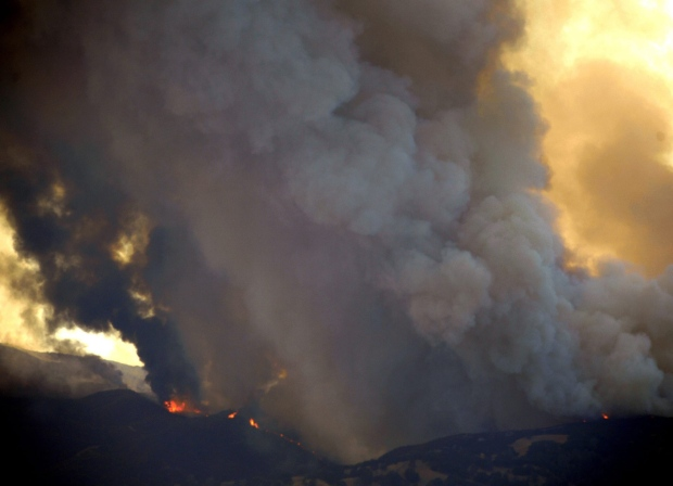 Flames erupt on the hills above Pleasants Valley Road, Tuesday, July 28, 2015, near Winters, Calif. (Joel Rosenbaum / The Vacaville Reporter via AP)