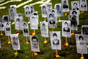 """Portraits of people who disappeared during the nation's 20 year civil conflict stand on the lawn at the """"Ojo que Llora"""" memorial, or """"Eye that Cries"""" memorial in Lima, Peru on Aug. 24, 2013. (Rodrigo Abd / AP Photo)"""