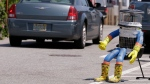 A car drives by HitchBOT, a hitchhiking robot in Marblehead, Mass. on July 17, 2015. (AP / Stephan Savoia)