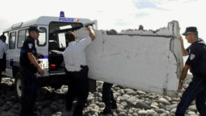 Officials load debris found on a remote island, believed to be from a Boeing 777 and possibly from MH370, into a police van.