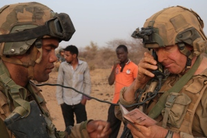 In this photo taken Sunday, June 21, 2015, a French soldier radios in the details of a man, left rear, taken from his driving license in the desert south of the village of Deliman, Mali. (Maeva Bambuck / AP Photo)