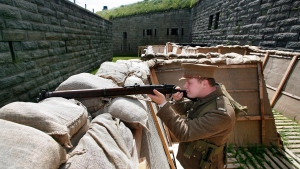 "Stephen Loney, portraying a Lance Corporal with the 25th Battalion, Nova Scotia Rifles,takes aim over some sandbags of a replica First World War trench at the Halifax Citadel on Thursday, July 16, 2015. Parks Canada and the Halifax Citadel National Historic Site will launch the First World War Trench Experience to commemorate the 100th anniversary of the composition of ""In Flanders Fields"" on July 18-19. THE CANADIAN PRESS/Darren Pittman"