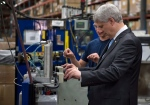 Conservative Leader Stephen Harper gets instructions on how to operate a machine that puts the finishing touch to a radiator while touring a industrial parts manufacture Monday, August 3, 2015 in Laval, Que. (Paul Chiasson/THE CANADIAN PRESS)