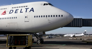 FILE - In this Oct. 9, 2012 file photo, a Delta Air Lines 747-400 airplane sits parked at Seattle-Tacoma International Airport in Seattle.
