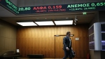 A man walks at the reception hall of the Athens' Stock Exchange as stock prices are on display on a ticker screen in Athens, Greece, on Aug. 4, 2015. (AP / Yorgos Karahalis)