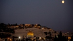 A supermoon rises over Jerusalem's Old City and the Dome of the Rock seen from the roof restaurant of the Notre Dame hotel on July 12, 2014. (AP / Dusan Vranic)