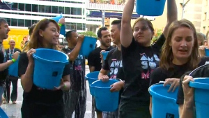 Participants dump ice-cold buckets of water over each other's heads in downtown Toronto on Tuesday, August 4, 2015, to start the Ice Bucket Challenge 2.0. The viral campaign raised $220 million worldwide for ALS last year.
