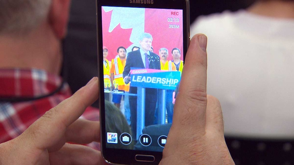 Conservative Leader Stephen Harper is seen on a smartphone as he makes a campaign announcement in the North York section of Toronto, Tuesday, Aug. 4, 2015.