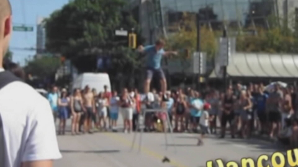 A street performer was balancing on a roller board on top of a large platform when a child ran out of the audience and tried to touch the precariously-placed cylinder. (YouTube/MotorcyclesVancouver)