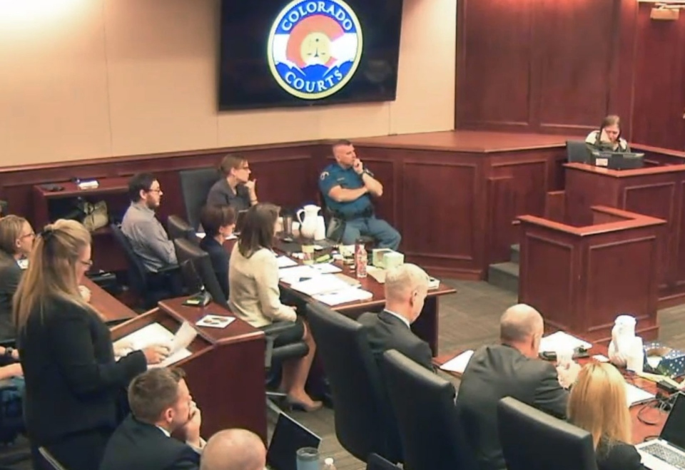 Cierra Cowden, right, cries while giving testimony about her memories of her father Gordon Cowden, who was killed by Colorado theater shooter James Holmes, who sits third from left in back in a gray shirt, during Holmes' trial, in Centennial, Colo., Wednesday, Aug. 5, 2015. (Colorado Judicial Department)
