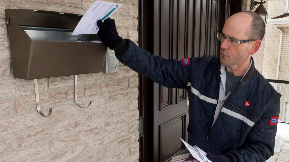 A letter carrier works in Montreal, on Thursday, March 5, 2015. (Ryan Remiorz / THE CANADIAN PRESS)