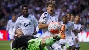 Seattle Sounders' Zach Scott, bottom, tries to keep the ball in bounds in front of Vancouver Whitecaps' Diego Rodriguez, centre, during the second half of CONCACAF Champions League soccer game in Vancouver, B.C., on Aug. 5, 2015. (Darryl Dyck / THE CANADIAN PRESS)