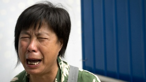Bao Lanfang, whose daughter-in-law, son, and granddaughter were aboard Malaysia Airlines Flight 370, cries as she protests outside the company's offices in Beijing on Aug. 6, 2015. (AP / Mark Schiefelbein)