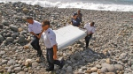 In this July 29, 2015, photo, French police officers carry a piece of debris from a plane known as a flaperon in Saint-Andre, Reunion Island. (AP Photo/Lucas Marie)