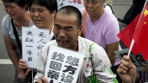 Relatives of the passengers aboard Malaysia Airlines Flight 370 that went missing on March 8, 2014, kneel down and cry in front of the media ahead of a briefing given by the airlines outside a help centre in Beijing on Aug. 7, 2015.