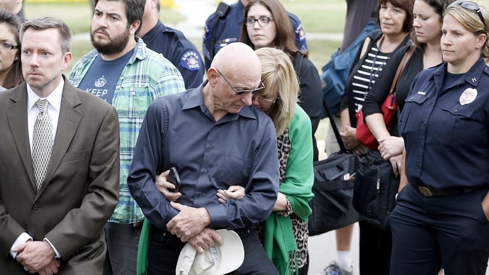 Lonnie and Sandy Phillips, center, whose daughter Jessica Ghawi was killed in the 2012 Aurora movie theatre attack, hold each other as they listen to District Attorney George Brauchler speak following the jury's decision outside the Arapahoe County District Court in Centennial, Colo., Friday, Aug. 7, 2015. (AP  / Brennan Linsley)