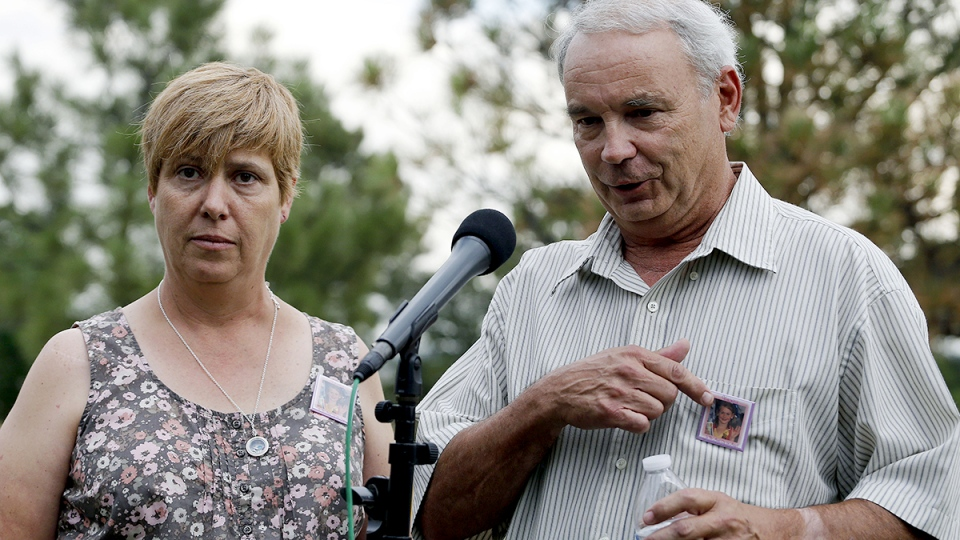 Robert and Sue Sullivan, whose 6-year-old granddaughter Veronica, whose picture is pinned to their chests, was killed in the theater shooting speak with the media outside Arapahoe County Courthouse after the jury failed to agree on whether James Holmes should get the death penalty Friday, Aug. 7, 2015. (AP / Brennan Linsley)