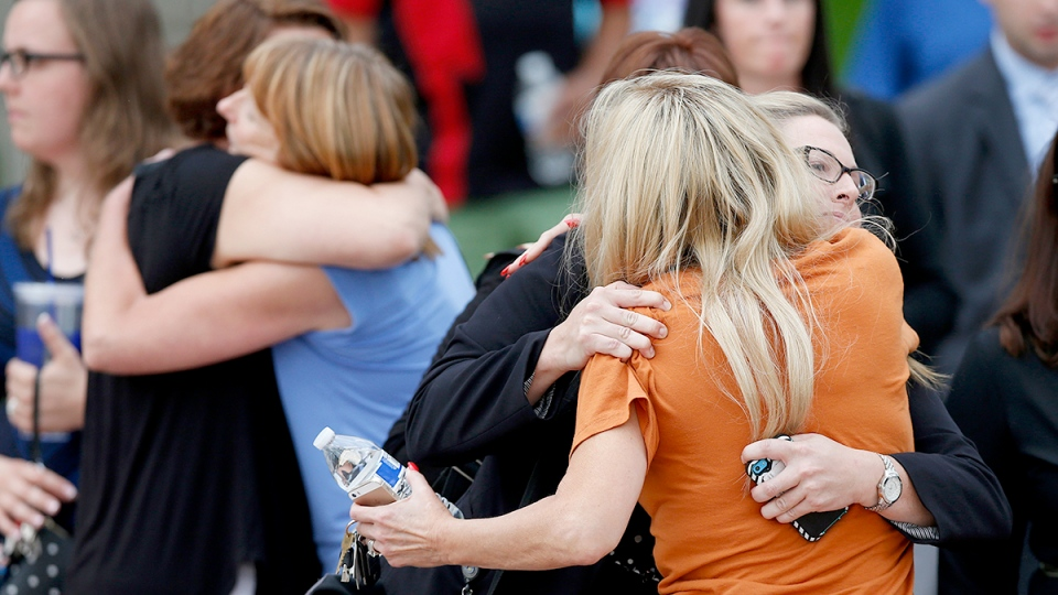 People embrace as they leave the Arapahoe County Courthouse after a jury failed to agree on whether theater shooter James Holmes should get the death penalty Friday, Aug. 7, 2015, in Centennial, Colo. (AP / David Zalubowski)