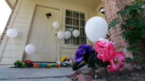 Flowers and balloons at a house where a family of six children and two parents were found dead in Houston, on Aug. 9, 2015. (David J. Phillip / AP)