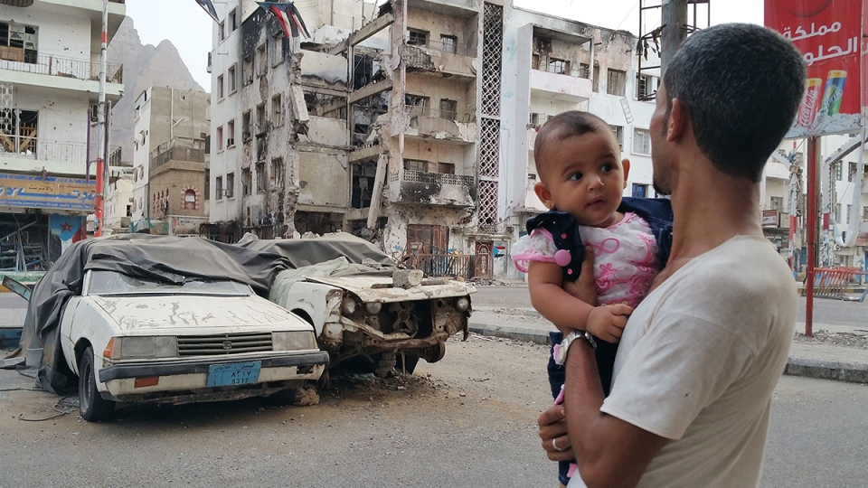 A Yemeni man carrying his daughter looks at a building destroyed during fighting against Houthi fighters in the port city of Aden, Yemen, Sunday, July 19, 2015. (AP / Ahmed Sameer)