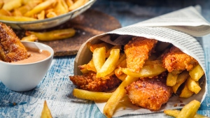 Chicken finders and fries are seen wrapped in a newspaper. (Shaiith / shutterstock.com)