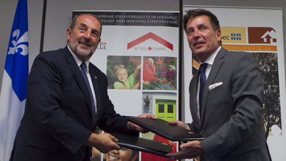 The Honourable Denis Lebel (left), and Pierre Moreau are shown in Quebec City, Monday, July 27, 2015, at the signing ceremony the Investment in Affordable Housing agreement. (MARKETWIRED / Canada Mortgage and Housing Corporation)