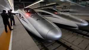 In this Oct. 26, 2010 file photo, a journalist photographs bullet trains of a new high-speed railway linking Shanghai and Hangzhou in Shanghai before the start of the service. (AP / Eugene Hoshiko, File)