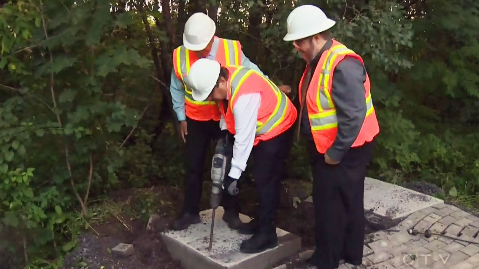 Montreal Mayor Denis Coderre drills concrete the site of a planned Canada Post community mailbox. (CTV)