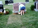A woman is seen pulling flowers from a grave site at St. Peter's Cemetery in London, Ont. in this image released by London police.