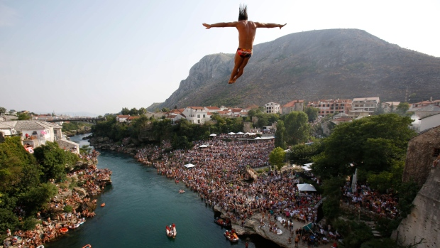 Competitors dive from the Old Mostar Bridge during the sixth stop of the Red Bull Cliff Diving World Series 2015, in Mostar, 140 kms south of Bosnian capital of Sarajevo, Saturday, Aug. 15, 2015. (AP / Amel Emric)