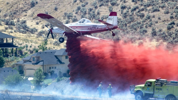 An Air Tractor Fire Boss turboprop dumps a load of retardant near a pair of Bureau of Land Management Boise District firefighters during a fire near Quail Hollow Golf Course in the Boise, Idaho foothills, Thursday, Aug. 13, 2015. (Kyle Green / Idaho Statesman)