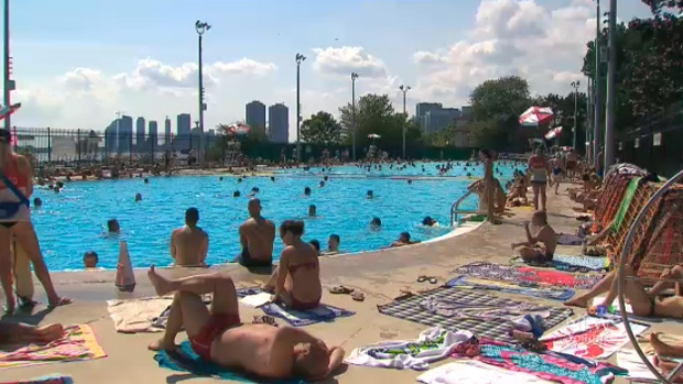 Sunbathers and swimmers visit a Toronto pool on Sunday, Aug. 16, 2015.