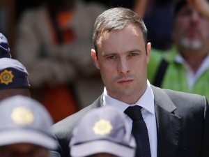 Oscar Pistorius is escorted by police officers as he leaves the high court in Pretoria, South Africa on Friday, Oct. 17, 2014.