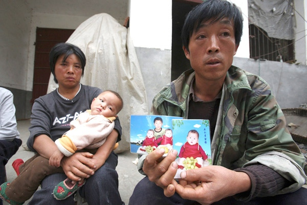 Li Xiaoquan, right, holds up a photo of his twin daughters at their home in Liti village, near Runan, central China's Henan province, on Sunday, Oct. 19, 2008. One of the twins, who had been drinking a brand of milk formula linked to the melamine scandal, died from kidney failure. (AP / Ng Han Guan)