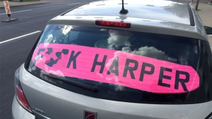 A four-door Saturn with this bright pink sign has been eliciting responses both online, and in person.