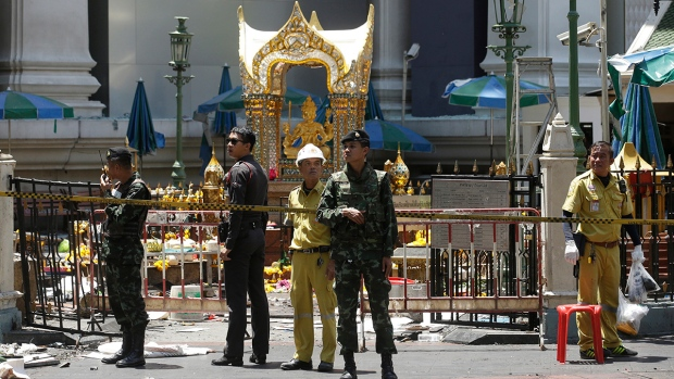 Police, soldiers, and other officials work near the statue of Phra Phrom, the Thai interpretation of the Hindu god Brahma, at the Erawan Shrine at Rajprasong intersection the day after an explosion in Bangkok, Thailand, Tuesday, Aug. 18, 2015. (AP / Sakchai Lalit)