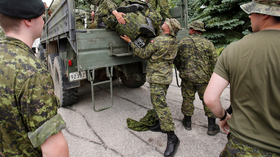 Military reserves arrive at Southport, Man. to assist with flood preparation from Portage La Prairie to St Francois Xavier Saturday, July 5, 2014. (John Woods / THE CANADIAN PRESS)