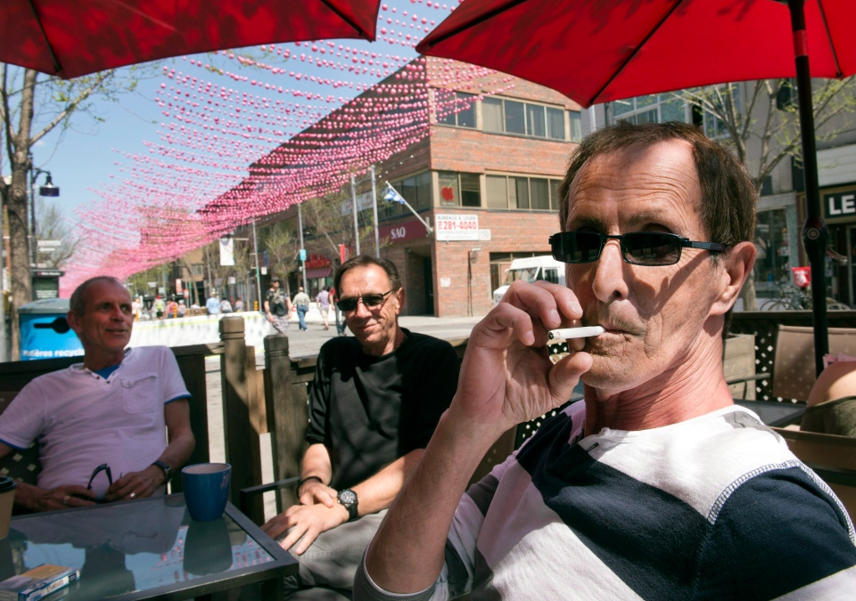 Robert Labelle, right, smokes a cigarette as his friends Gilles Garand, left, and Michel Casey, centre, look on on Wednesday, May 6, 2015 in Montreal. (Ryan Remiorz / The Canadian Press)