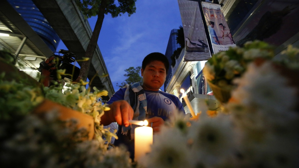 A Thai man lights a candle near the Erawan Shrine at Rajprasong intersection the day after an explosion in Bangkok, Thailand, Tuesday, Aug. 18, 2015. (AP / Sakchai Lalit)