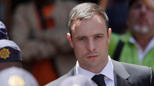 Oscar Pistorius is escorted by police officers as he leaves the high court in Pretoria, South Africa on Oct. 17, 2014. (The Canadian Press/AP, Themba Hadebe)