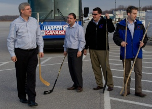 Stephen Harper is seen with former Conservative staffers, left to right, Dimitri Soudas, Mike Beaton, and current staffer Ray Novak following an impromptu ball-hockey game on the tarmac prior to boarding his campaign plane in Kitchener, Ont., on Saturday, April 9, 2011. (Sean Kilpatrick / THE CANADIAN PRESS)