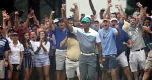 Tiger Woods reacts after holing out a chip shot on the 10th hole at Wyndham Championship golf tournament in Greensboro, N.C., on Thursday, Aug. 20, 2015. (AP Photo/Chuck Burton)