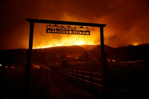 Fire burns on the ridge above a ranch on Twisp River Road in Twisp, Wash., on Wednesday, Aug. 19, 2015. Authorities on Wednesday afternoon urged people in the north-central Washington town to evacuate because of a fast-moving wildfire. (AP / Ted S. Warren)