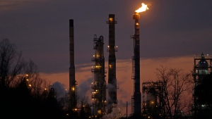 In this Feb. 13, 2015 file photo, stacks and burn-off from the Exxon Mobil refinery are seen at dusk in St. Bernard Parish, La. (Gerald Herbert / AP Photo, file)